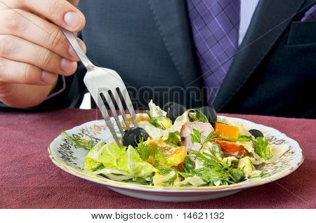 Man Eating Salad. Hand With Fork Closeup