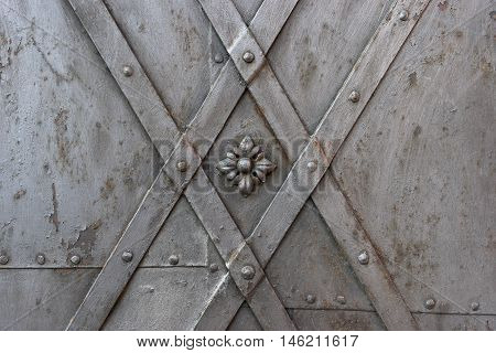 A fragment of an old metal door with rivets