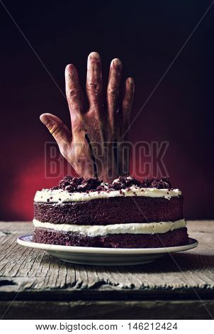 a red velvet cake topped with a bloody hand in a scary scene for halloween, on a rustic wooden table
