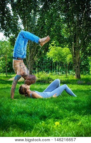 Man and woman yogi doing various yoga poses in a pair. Healthy yoga lifestyle. Yoga in the summer park, outdoor.
