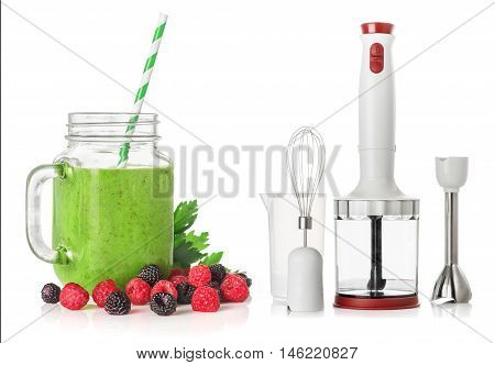 Green smoothies in a glass jar with raspberries and blackberries and Immersion blender isolated on white background healthy eating concept
