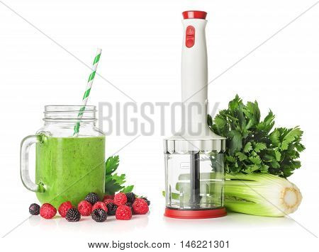 Blender stems and leaves of celery green smoothies with raspberries and blackberries salad isolated on white background healthy eating concept