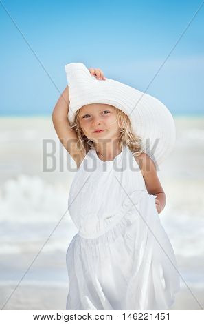 Little caucasian white serious girl two years old in a white mothers dress and hat at the beach near the sea