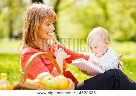 Happy mother with son sitting down on green grass field and read fairytale