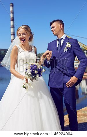 Bride and groom holding hands in the port. Beautiful fabulous happy bride and stylish groom having fun.