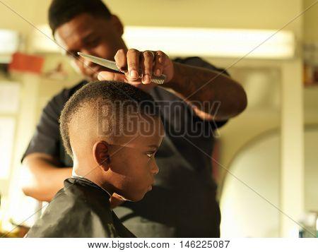 little boy in barbershop getting head shaved