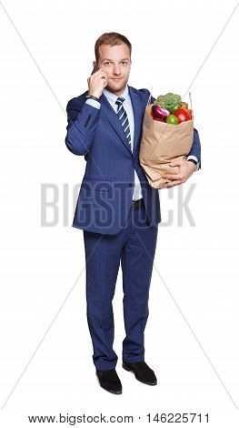 Smiling young businessman calls mobile phone with shopping paper bag with groceries, vegetables and fruits, isolated at white background. Healthy food shopping. Full length portrait of hurrying buyer