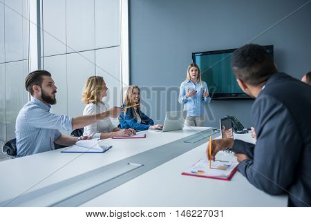 Attractive woman presenting her business ideas to the team.