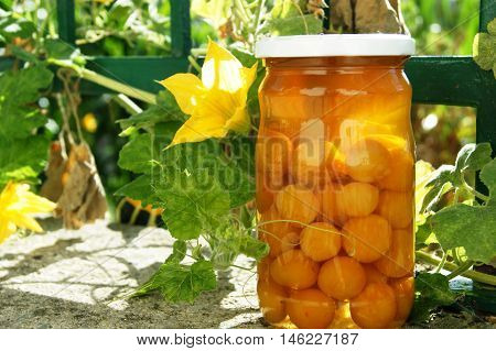 Glass jar with yellow compote of plums