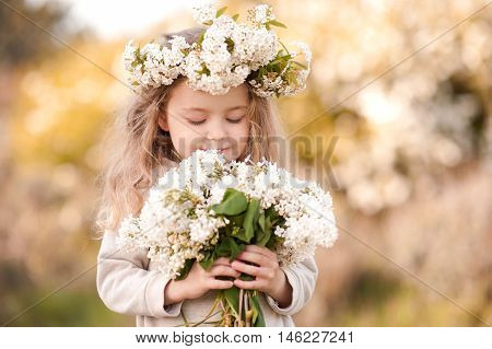 Smiling kid girl 4-5 year old holding white lilac flowers outdoors.