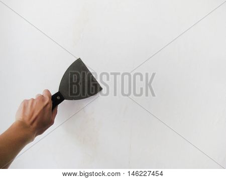 Hand holding putty knife patching holes repair damage in white wall. Renovation process in apartment room background