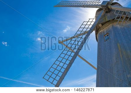 Wooden windmill on blue sky background with copy space