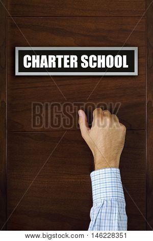 Charter school concept male hand knocking on the door
