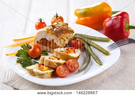 Baked chicken rolls with tomato and paprika on white plate on the white wooden table