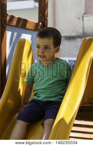 Adorable Little Boy Playing On A Slide In A Kids Outdoor Playground Sitting At The Top