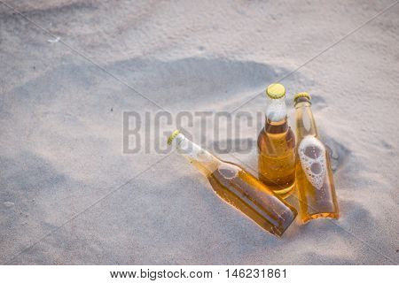 Three Cold Beer Bottles In The Sand