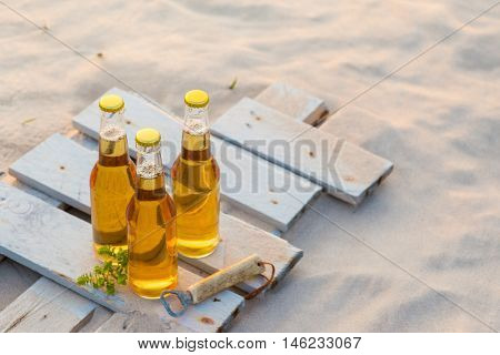 Three Beer Bottles Standing On The Rustic Wooden Board