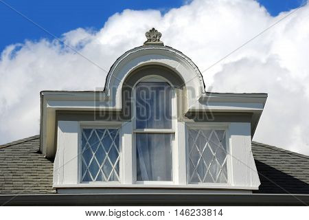 Three glass windows set inside arched dormer on elegant Victorian home in Stoughton Wisconsin.