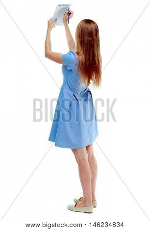 back view of stands woman takes notes in a notebook. girl watching. Isolated over white background. Skinny girl in a blue dress writes in notebook holding it over his head.