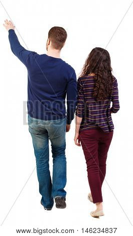 Back view of walking young couple (man and woman) pointing. Rear view people collection. Swarthy girl and the bearded man on the move shows his hands up.