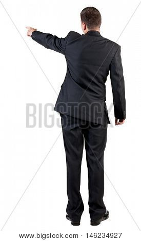 Back view of pointing business man. gesticulating young guy in black suit. Rear view people collection.  Isolated over white background.  backside view of person.