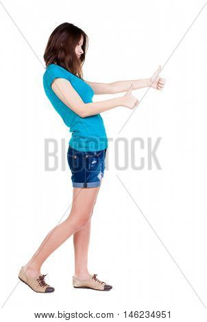 Back view of  woman thumbs up. Rear view people collection. backside view of person. Isolated over white background. slender brunette in a shorts shows the symbol of success or hitchhiking