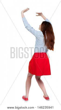 back view of woman protects hands from what is falling from above. Long-haired brunette in red skirt protects hands from above.