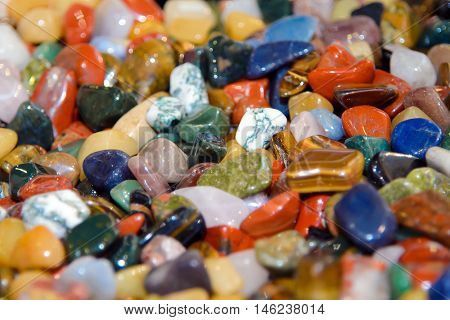 Scattering of colorful smooth stones. Background color of minerals. Collection of stones. Round precious and semi-precious minerals. Polished minerals. Beautiful natural stones. Geology and geography.