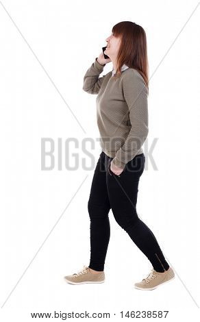 side view of a woman walking with a mobile phone. back view of girl in motion. Laughing girl with a phone in his hand goes to the right.