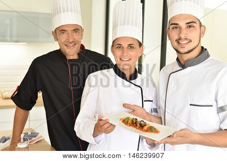Young chefs presenting dish to teacher