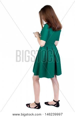 back view of standing young beautiful woman using a mobile phone or tablet computer. slender brunette in a green short dress stands sideways looking at the phone.