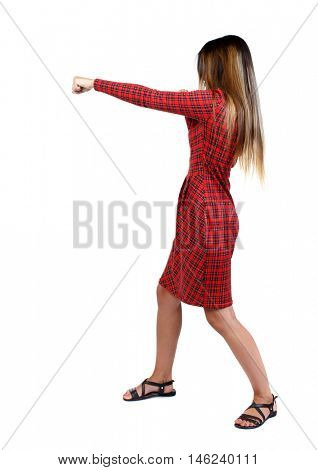 skinny woman funny fights waving his arms and legs. girl in red plaid dress stands sideways and punches.