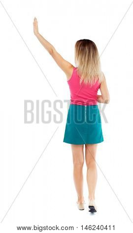 Back view of beautiful woman welcomes. Young teenager girl in jeans hand waving from. Isolated over white background. Blonde in a red sweater and green skirt went off waving.