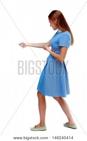 back view of standing girl pulling a rope from the top or cling to something. girl watching. Isolated over white background. Skinny girl in a blue dress drags a side load on the rope.