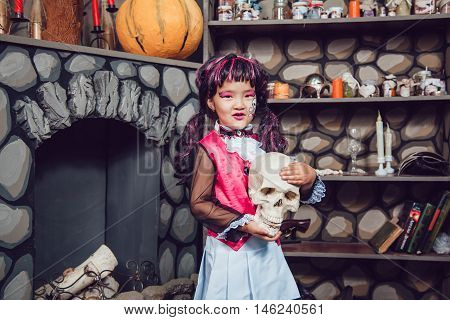 Girl in a witch costume is a skull in his hand in the scenery helloween