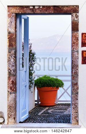 Open door in Fira Santorini Greece. Sea and volcano on background