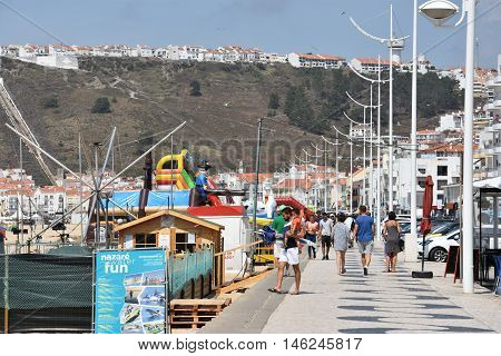 NAZARE, PORTUGAL - AUG 24: Beach at Nazare fishing village in Portugal, as seen on Aug 24, 2016. It has become a tourist attraction, advertising as a picturesque seaside village.