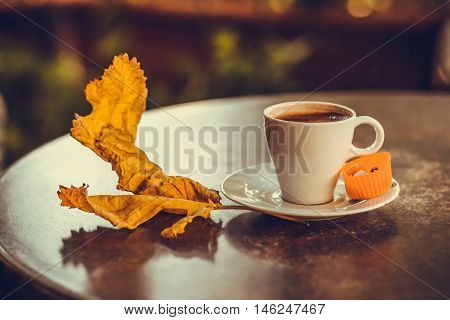 Turkish coffee in a white cup with candy in paper and dry yellow autumn leafe on the table. Photo toned with shallow depth of field