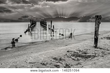 Coastal landscape with remains of old marine pier that was used for traditional fisheries many years ago, Northern Sea, Europe at the Baltic Sea in 20 century