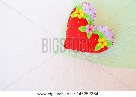 Hand made felt heart. Symbol of Valentines Day. Beautiful heart handmade on green and white background