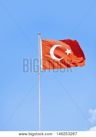 Vertical photo of Turkish flag waving in the sky