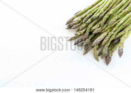 A heap of green asparagus isolated on white background with lots of copy space.