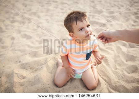 little boy eat icecream from mothers hand; mom feeding small kid with ice cream;