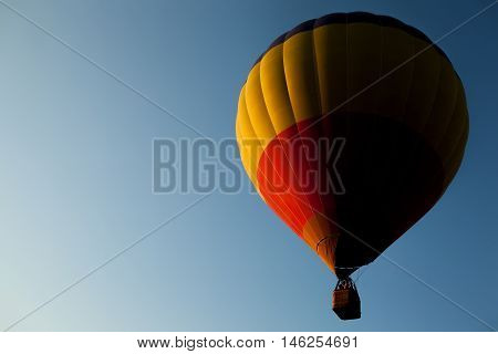 air balloon flying in clear blue sky; aircraft flies high in atmosphere;
