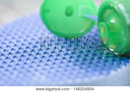 detail of dishwashing liquid and blue sponge