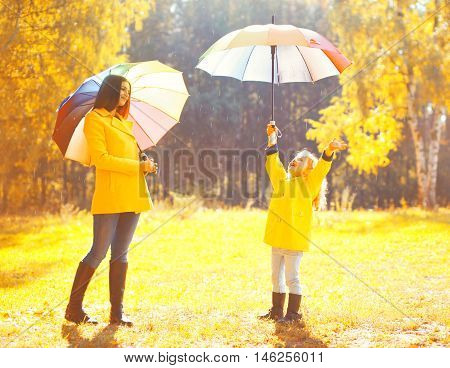 Moment Of Happiness! Happy Family With Umbrellas In Sunny Autumn Rainy Day, Young Mother And Child I