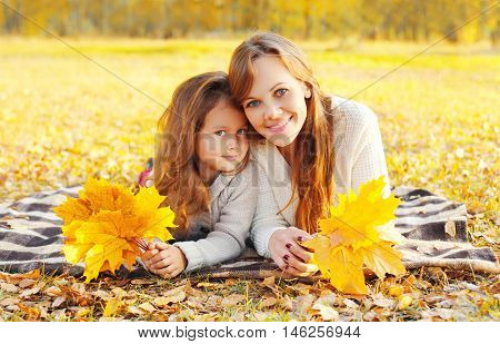 Portrait Happy Smiling Mother And Child Together With Yellow Maple Leafs Lying On The Plaid In Sunny