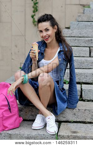 Woman Eating Ice Cream While Sitting On The Granite Steps