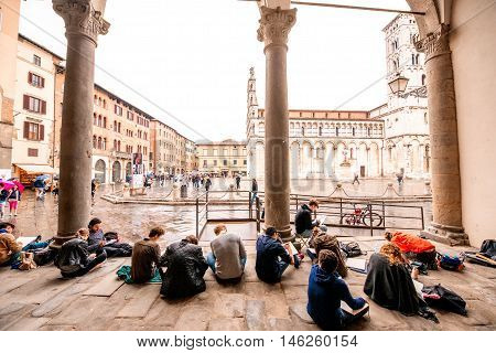 Lucca, Italy - June 03, 2016: Students sit near Pretorio palace and draw architectural details on the main square in Lucca old town in Italy