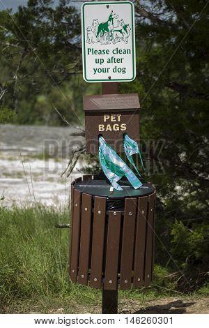 Pet waste trash bin at the trail head of a hiking trail.